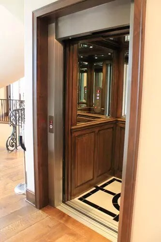 Custom residential elevator with wood and mirror car panels