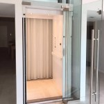 Symmetry Home Elevator with painted white interior and glass door with stainless steel handle. Installed by Area Access