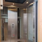 Symmetry Home Elevator in glass and stainless-steel, with wrap around gate installed by Morning Star