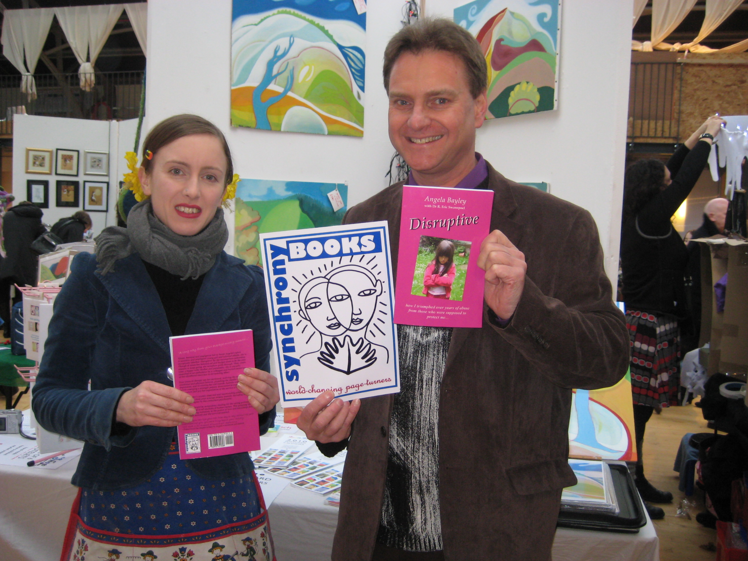 Clare Galloway and Eric Swanepoel display the Synchrony Books logo, designed by Clare, and copies of 'Disruptive', the cover of which was designed by Vroni Holzmann.