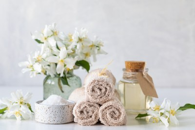 Spa concept of jasmine oil, with bath salt and flowers on a white background. Spa and wellness still life.