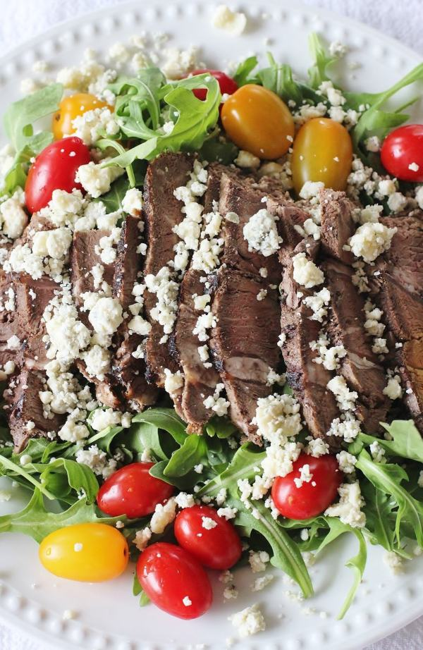 Sirloin Steak and Arugula Salad. Thinly sliced cold sirloin steak sits atop lightly dressed arugula. Cherry type tomatoes are added to the side and the blue cheese crumbles get sprinkled on top.