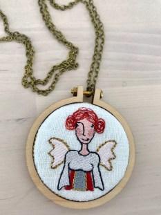Den søteste gave fra Fru Blomgren - denne skytsengelsen er brodert på en symaskin og er formet som en liten medaljong