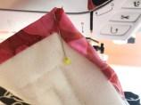 Stoffet foldes til et hjørne på 45 grader både under og oppe. Fest med en knappenål som er skråstilt for enklere å fjerne den når du syr hjørnet