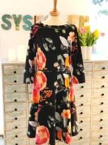 Kjolen er sydd i en storblomstrete bomullsjersey, har 3/4-lange ermer, båthals og vidde i skjørtet