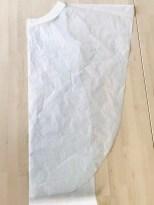Ponchoen har en ganske slank form. Den når meg til albuen og skråner hele veien i en slak bue ned til kneet