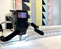 Med en longarmmaskin går det litt lettere når man quilter da hele quilten spennes opp i en ramme og maskinen er den som beveger seg