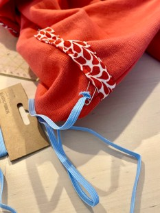 Raglan jerseykjole med tittekant og buet fald