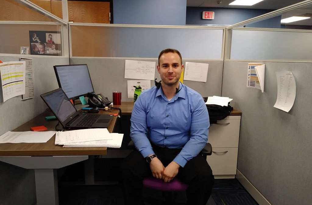 Ben Bentley, new team member, sitting at his desk in the cubicle