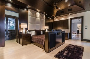 Beauty Rest Another bedroom features a similarly dark palette, but trades white ceilings for deeply-hued wood, and benefits from shuttered doors to allow light in—or shut it out for a good night's sleep