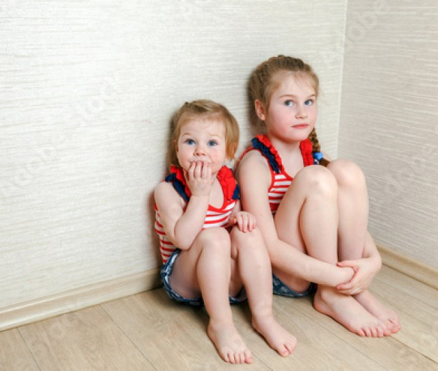 Two Barefoot Girls Sit On The Floor In The Corner Of The Room