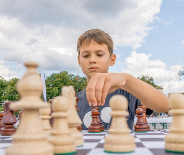 Kid Playing Chess At Chessboard Outdoors Boy Thinking Hard On Chess Combinations