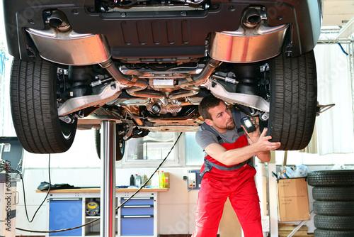 KFZ Mechaniker prüft Bremsen und Reifen am PKW