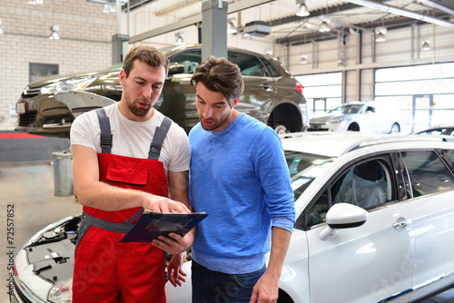 KFZ Mechaniker mit Kunden in Werkstatt
