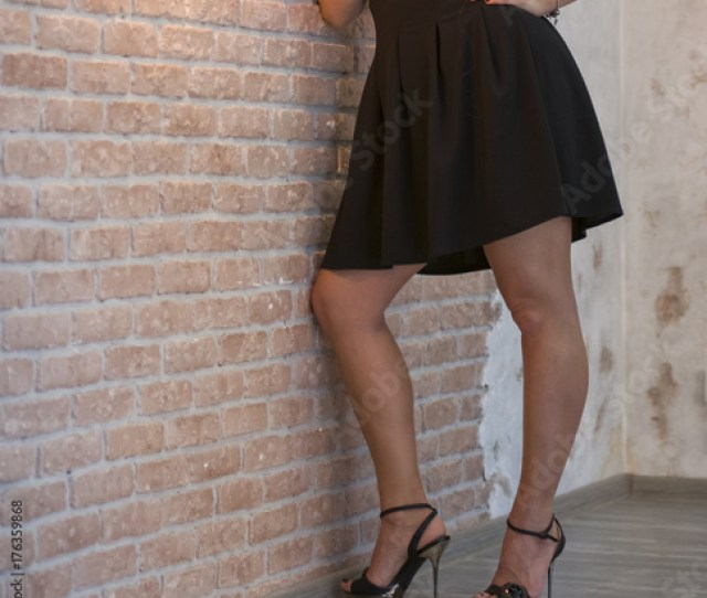 Girl And Beautiful Beautiful Sexy Legs In Heels In A Black Dress Against A Brick Wall