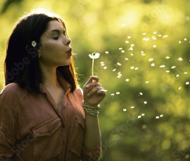 Young Teen Girl Blowing Dandelion