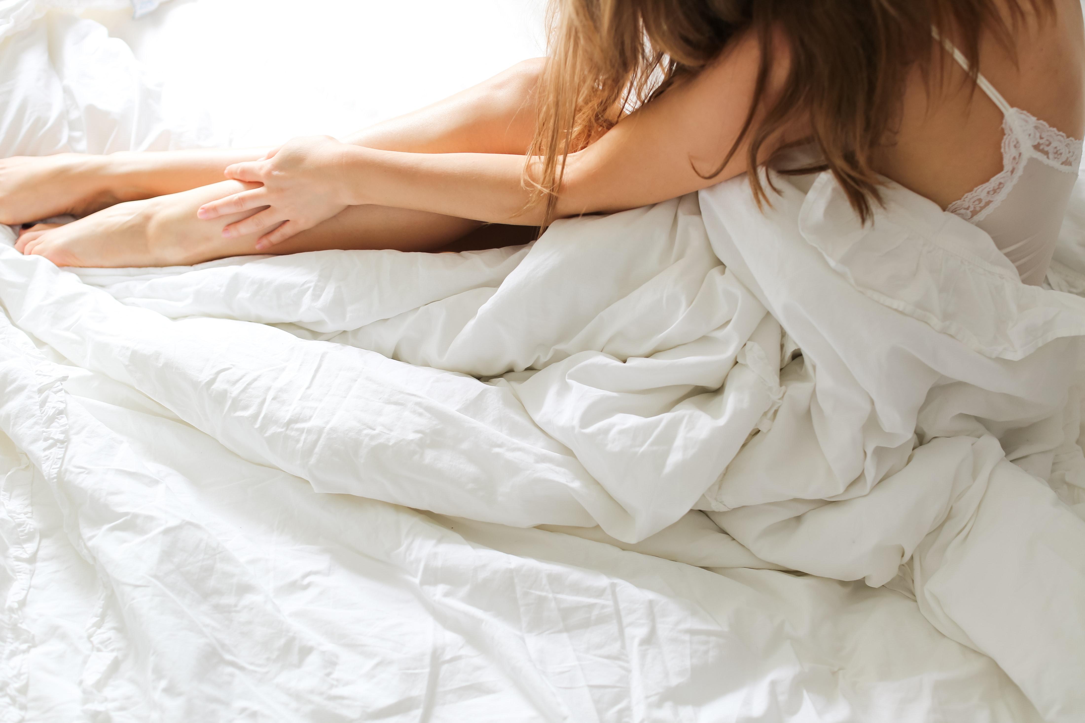 Topless mujer acostada en la cama cubierta con una manta blanca