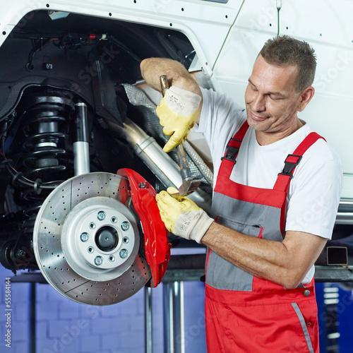 Car mechanic in a garage fixing the brake
