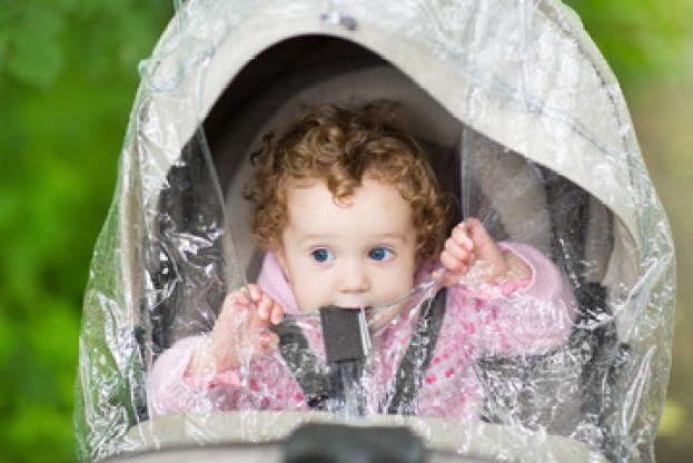 Cute curly baby girl sitting in a stroller under a rain cover