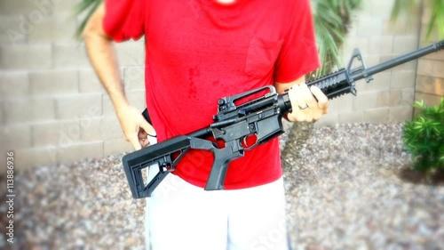 """A man holding an AR-15 rifle shows how quickly the gun ..."