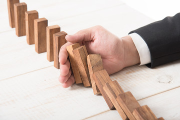Businessman hand trying to stop toppling dominoes on wood,stop domino effect