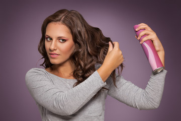 young lady applying hair spray for dandruff and dry scalp