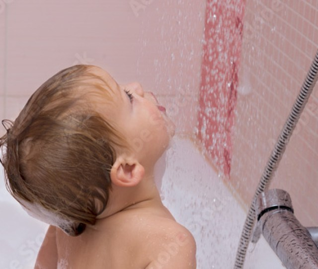 Cute Happy Baby Boy With Blonde Curly Hair In Shower Standing Under Water Jet In The