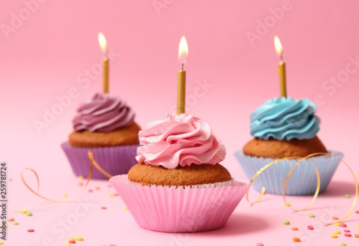 Delicious Cupcakes With Candles On A Colored Background Festive