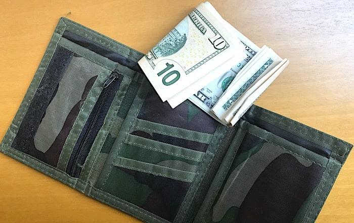三つ折り財布と折れたドル紙幣の画像