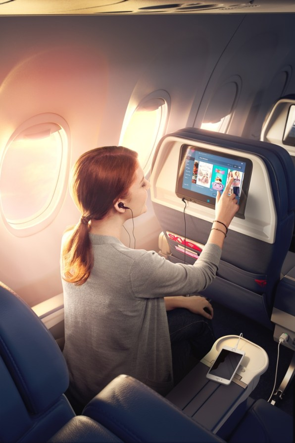Female customer using the IFE while her phone is charging on the console on a Boeing 737-900ER (739).- These images are protected by copyright. Delta has acquired permission from the copyright owner to the use the images for specified purposes and in some cases for a limited time. If you have been authorized by Delta to do so, you may use these images to promote Delta, but only as part of Delta-approved marketing and advertising. Further distribution (including proving these images to third parties), reproduction, display, or other use is strictly prohibited.