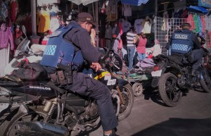 Police sit on motorbikes outside Tepito market