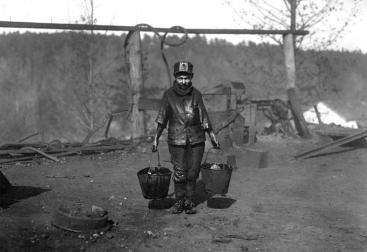 "Shorpy Higginbotham, a ""greaser"" on the tipple at Bessie Mine, of the Sloss-Sheffield Steel and Iron Co in Alabama. He said he was 14 years old, but it is doubtful. He carries two heavy pails of grease, and is often in danger of being run over by the coal cars. Photographed in December of 1910."