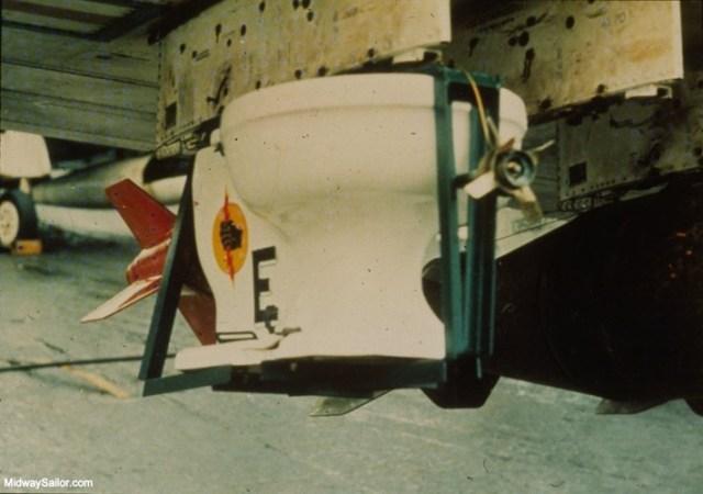 """Chiếc toilet đã được """"chế"""" thành một quả bom với kíp nổ và các cánh đuôi. Nó còn được gắn phù hiệu của Phi đoàn cường kích 25 trước khi gắn lên giá bom của một chiếc Máy bay Skyraider A-1H mang biệt danh """"Con Hổ Giấy II""""."""