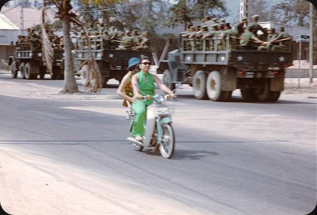 Hai quý bà ngồi Honda Dame C50 đi ngang qua các xe tải chở lính Mỹ.