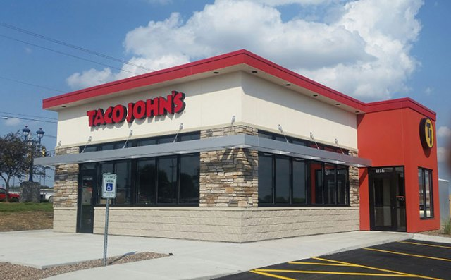An exterior of a Taco John's, with some of the parking lot visible.
