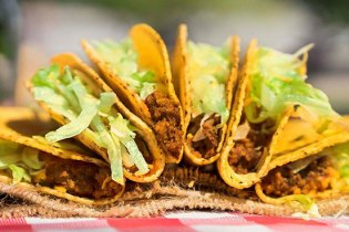 A line-up of six ground beef tacos topped with lettuce are fanned out atop a red-checkered tablecloth.