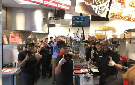 A group of uniformed employees in a kitchen turn toward the camera smiling with a thumbs-up.