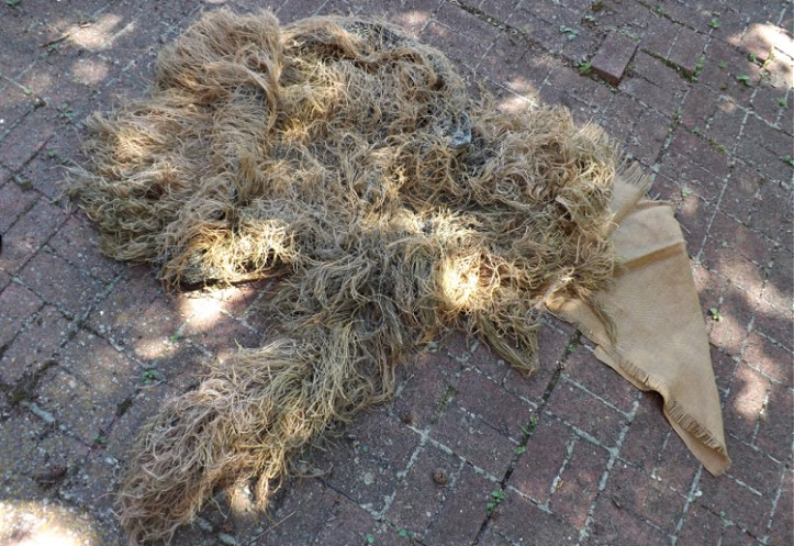 partially completed ghillie suit with burlap strings attached to netting.