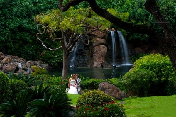 bride and groom embracing at the waterfall at the Hyatt Regency Maui Resort & Spa