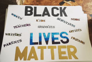 """A sign reads """"black lives matter"""" with smaller text reading """"womxn, kids, teachers, grannies, sisters, parents, scientists, nerds, artists, friends."""""""