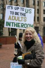 """A person holding a sign that reads """"It's up to us to be the adults in the room."""""""