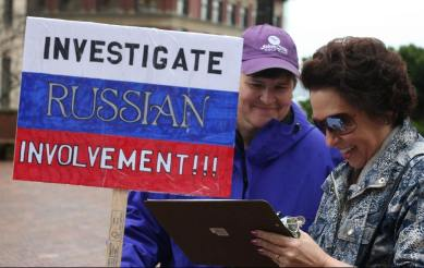 "A sign drawn on top of the Russian flag reads ""Investigate Russian Involvement!"""