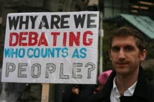 "A person holds a sign reading, ""why are we debating who counts as people?"""