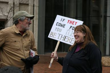 """A person holds a sign that says, """"if they come for you, I'll be there."""""""