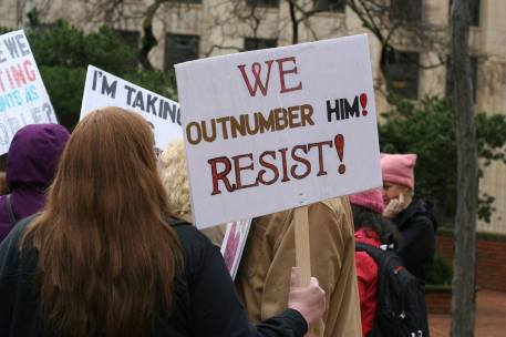 """A person holds a sign that says, """"We Outnumber Him! Resist!"""""""