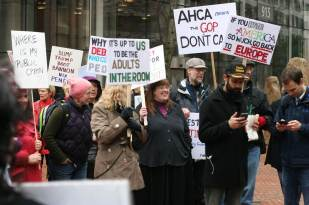 A group of people hold protest signs.