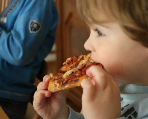 Kinder beim Pizza essen