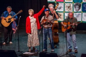 DARLING PERSONS--Maggie Peterson gives Dean Webb a hand as longtime Doug Dillard Band members Ginger Boatwright and Roger Rasnake play guitar and Buddy Griffin plays bass during the Doug Dillard Memorial Concert. Photo by Hobart Jones.