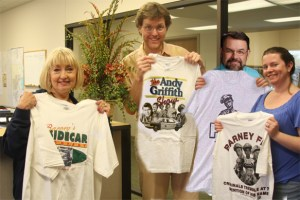 Kind Behind the Eyes-- Friends at South Yukon Church of Christ show some of the T-shirts they received for tornado relief. Pictured (l-r) are: Karla Stockton (office coordinator), Clyde Hughes (Mayberry Nut.), Perry Greene (minister) and Holly Gooch (office technician).