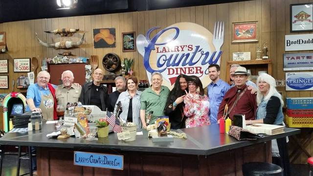 "EATIN' SPEAKS LOUDER THAN WORDS--Rodney Dillard (green shirt) and the Dillards band are surrounded by and mingled among the cast of ""Larry's Country Diner"" during a taping in Nashville in April. The episode premiered on the RFD Channel earlier this month."
